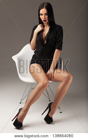 Fashion shot of a beautiful sexy brunette woman with long straight hair black shirt and black shoes sitting on the chair