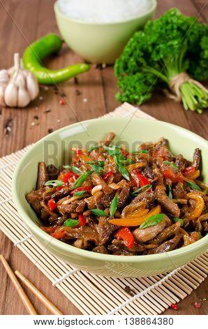 Stir fry pork sweet peppers onions and garlic. Asian cuisine