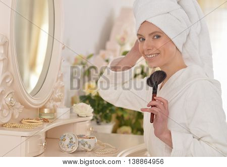 Young attractive woman doing make up after shower at boudoir