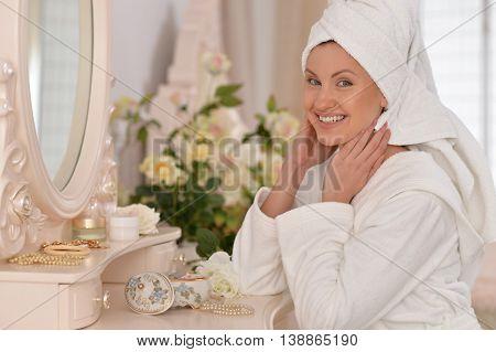 beautiful young woman wearing a white bathrobe near mirror