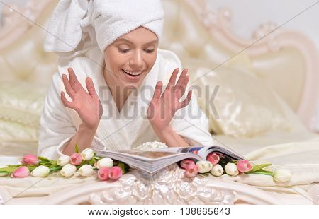 beautiful young woman wearing a white bathrobe  reading magazine in bed