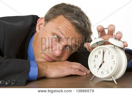 Businessman Leaning On Desk Watching Clock