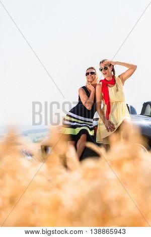Women having joyride in convertible car having rest at grain field enjoying the landscape