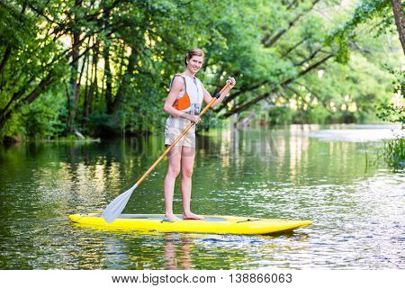 Woman paddling with surfboard sup on forest river