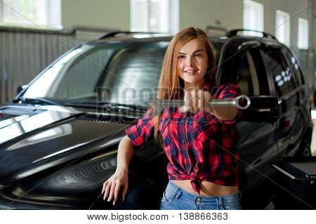 Female mechanic at work. auto service station. Young sexy brunette woman working in the garage.