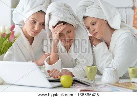 beautiful young women wearing a white bathrobes with laptop  and  tea at home