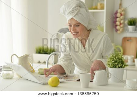 beautiful young woman wearing a white bathrobe with laptop