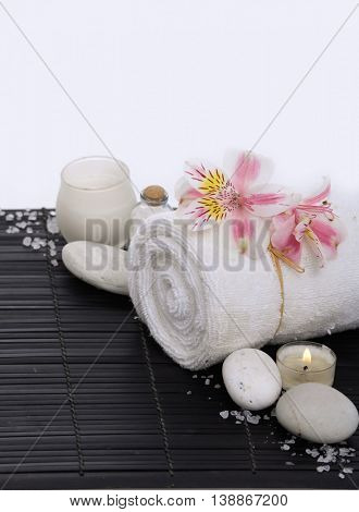 Spa setting on mat with orchid on roller towel