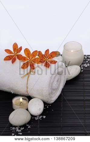 Spa resort -candle with orchid ,towel and stone on mat