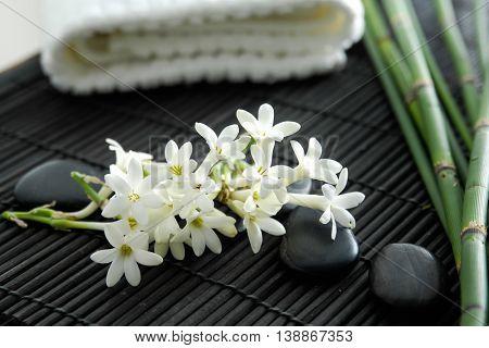 Spa resort â?? bamboo grove, flower, stones, towel on mat
