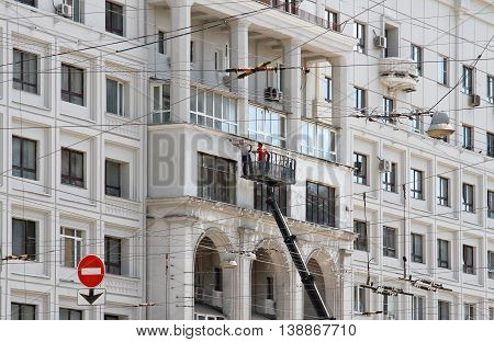 RUSSIA MOSCOW - JUNE 18 2015: Two construction workers in bucket of crane vehicle are reconstructing the facade of building in Moscow