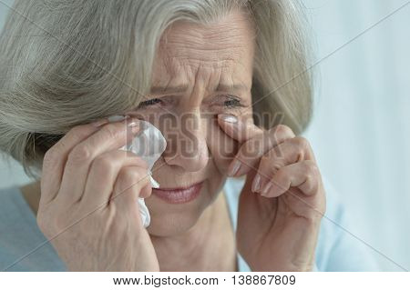 Portrait of a crying senior woman close-up