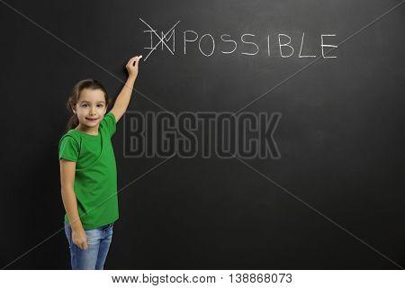 Smart little girl writing in a blackboard, with copy space