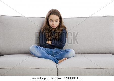 Little girl sitting on a couch and upset with something