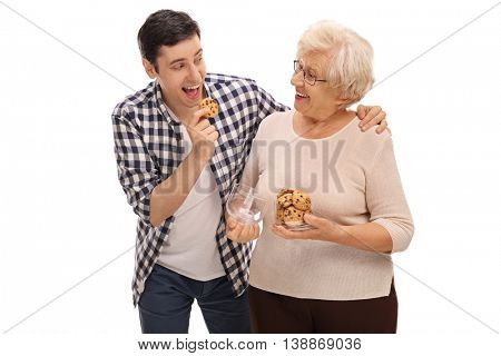 Senior lady giving homemade cookies to a young man isolated on white background