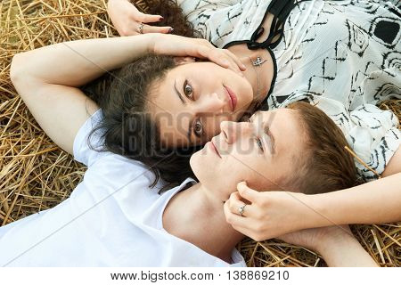 happy young couple lie in straw, wheaten field at evening, romantic people concept, beautiful landscape, summer season