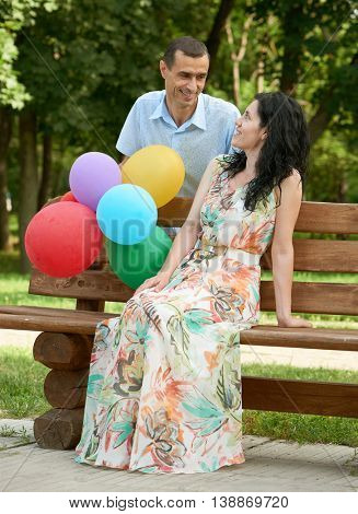 Happy romantic couple with balloon sit on bench in city park and posing, summer season, adult people man and woman
