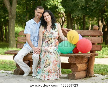 Happy romantic couple sit on bench in city park and posing, summer season, adult people man and woman