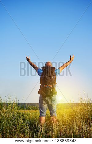 Back view of aged man in casual clothes with rucksack standing with hands lifted on the background of beautiful sunset in the field
