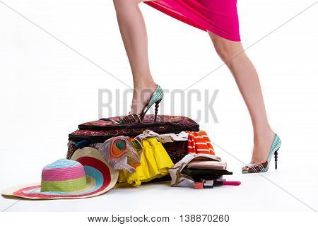 Lady's leg on filled suitcase. Striped hat beside filled suitcase. Need one more bag. Only essential things.