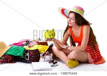 Woman sits near filled suitcase. Lady holds green piggy bank. Let's travel, my friend. Wealth gives opportinities.