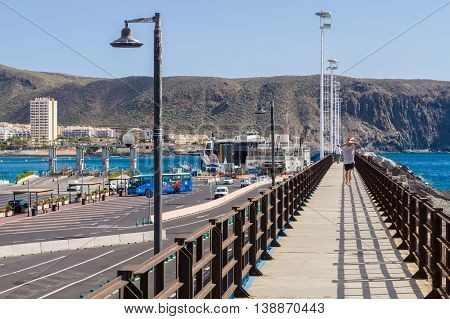 LOS CRISTIANOS SPAIN - JANUARY 19 2016: Infrastructure of Los Cristianos city harbor. Pier using as viewing platform for tourist.