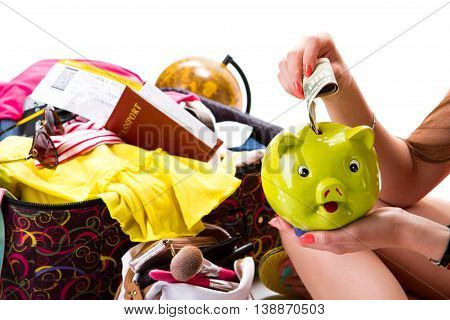 Lady's hand holds piggy bank. Passport on suitcase with clothes. Costs for summer trip. Money box of lime color.