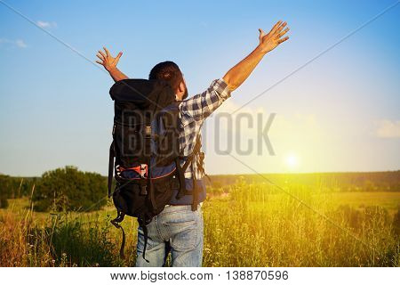 Back view of man in casual clothes with rucksack who is standing in the field with his hands lifted enjoying the beauty of landscape and sunset