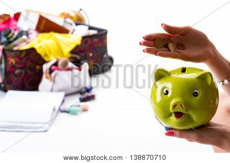 Girl's hand holding piggy bank. Coins and green money box. Time to count the savings. Lots of luggage for vacation.