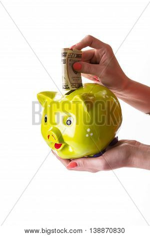 Girl's hand holds money box. Piggy bank on white background. Wealth in a box. Vacation will require great expenses.
