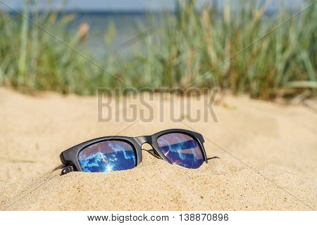 Reflecting sun glasses on sandy beach. Sea and grass on blurred background
