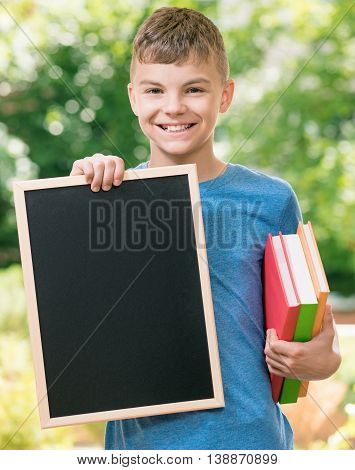 Outdoor portrait of happy teen boy 12-14 year old with small blackboard and books. Back to school concept.