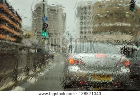 Abstract view  of the city under rain through the wet car windscreen. The image was made in Tel Aviv in February.