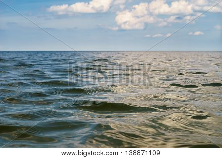 Open sea wavy water surface with cloudy sky on blurred background. Selective focus low angle view