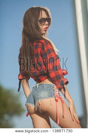 Portrait of the young beautiful smiling woman outdoors enjoying summer sun. Young woman outdoors portrait. Woman in jeans shorts and red shirt. Sexy woman buttocks.