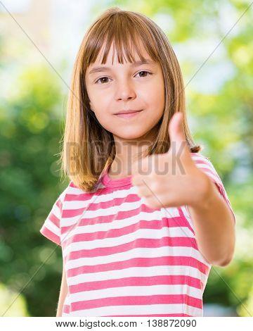 Portrait of happy girl 10-11 year old showing thumb up gesture. Beautiful schoolgirl posing outdoors.