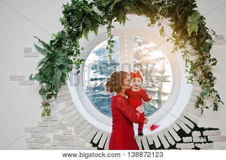 Mom And Daugter At Red Dress Background Circle Window With A Brick Facade