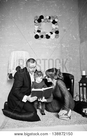 Happy Family With Daughter Read The Old Book On Rugs Background Vintage Room With Decor