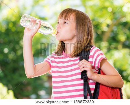 Outdoor portrait of happy girl 10-11 year old drinking fresh water from a bottle. Back to school concept.