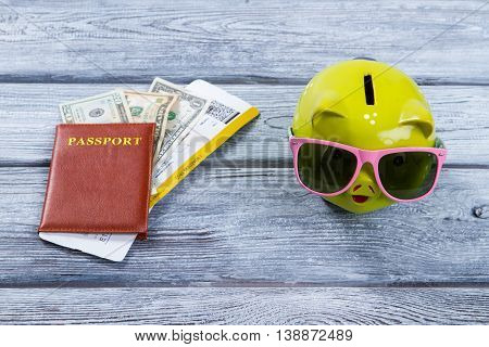 Brown passport and money box. Piggy bank in sunglasses. Luxury summer vacation abroad. Dreams shall come true.