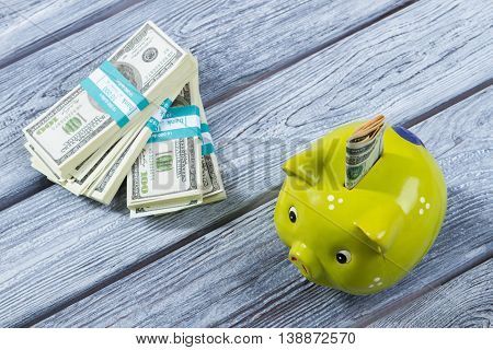 Folded dollars in money box. Piggy bank near money bundles. Don't waste all money. Small savings for the vacation.