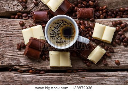 Coffee cup and chocolate. Coffee beans on wooden background. Flavor of fresh americano. Eat and drink with pleasure.