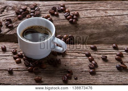 Steaming coffee cup. Dark-colored coffee beans. Good old tradition. Short break for coffee.