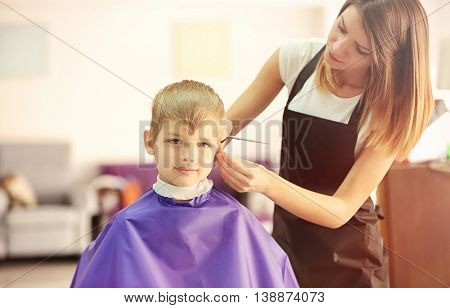 Hairdresser making hairstyle to child on blurred background