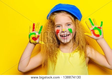 Cute laughing little girl with painted colorful hands over bright yellow background. Happy childhood.