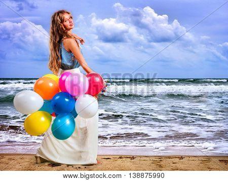 Girl keeps colored balloons walk on sea beach. There waves on sea beach.