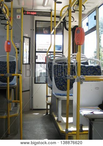 Interior of empty public european city bus without passengers during summer