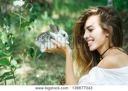 Pretty Young Woman Holds Rabbit