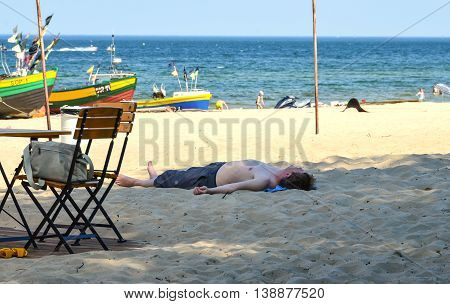 Sopot-Poland June-2016 Tired man lying down on sand in shadow spot on the beach at Baltic sea. Ilustrative editorial photo.
