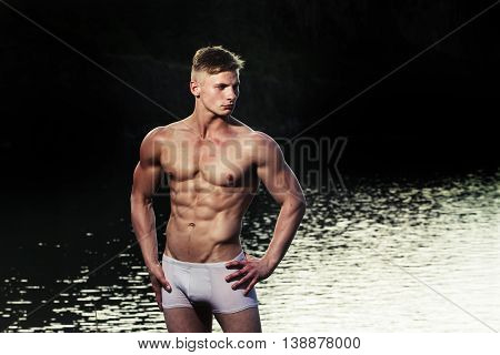 handsome young macho man with muscular sexy body and six packs on torso in pants sunny day outdoor on water natural background